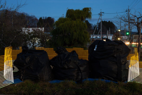 A special light painting tool reveals radiation levels around abandoned bags of contaminated waste outside Mr Hiroshi Kanno's former home in Kusano, Iitate, Fukushima. Here we see radiation levels between 0.38uSv/h and 0.51uSv/h, with yellow showing spots elevated above the government decontamination target of 0.23 uSv/h. Greenpeace/Greg McNevin
