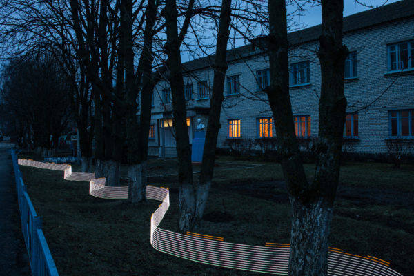 A special light painting tool displays radiation levels in real-time at a school in Starye Bobovichi (Старые Бобовичи). Here white light shows contamination levels up to 0.23uSv/h, while orange highlights elevated levels – up to 0.30uSv/h around these trees. 30 years after the 1986 Chernobyl nuclear disaster, the schoolyard still contains areas of elevated radiation levels. This image has not been digitally manipulated outside of minor contrast and exposure adjustments. Greenpeace/Greg McNevin
