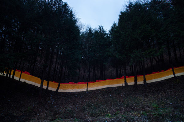 A special light painting technique reveals radioactive contamination in a forest bordering the Sato family house in Iitate. The forest has been decontaminated, but authorities only do 20 metres in from the edge, with everything beyond falling under the responsibility of a seperate government agency. Forest beyond the 20 metre boundry is not decontaminated, leading to constant re-contamination of the lower forest and house that borders it. Here we see radiation levels between 0.97uSv/h and 1.4uSv/h, with yellow showing spots elevated above the government decontamination target of 0.23 uSv/h, and red showing above 1uSv/h. Greenpeace/Greg McNevin