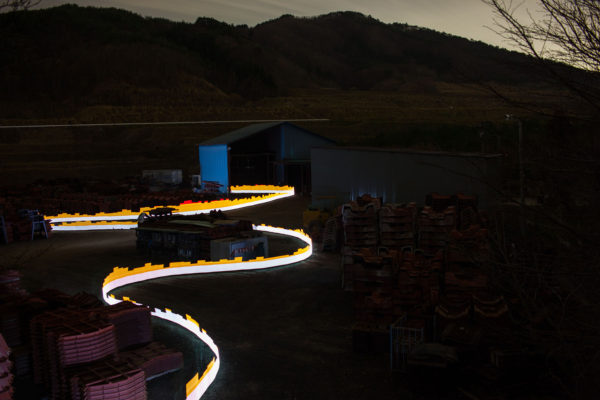 A special light painting technique reveals radioactive contamination at the Sato family's breakwater barrier factory in Iitate. Surrounded by forest and a growing stockpile of waste from decontamination work, the property remains contaminated despite being cleaned up. Here we see radiation levels between 0.22uSv/h and 1.15uSv/h, with yellow showing spots elevated above the government decontamination target of 0.23 uSv/h, and red showing above 1uSv/h. Greenpeace/Greg McNevin