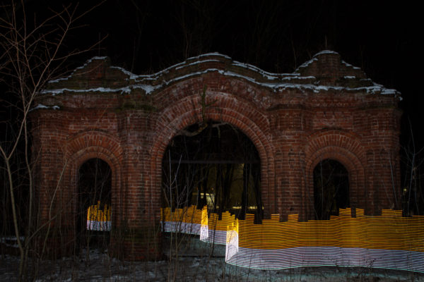 A special light painting tool displays radiation levels in real-time at a gateway to a former church in the centre of Starye Bobovichi (Старые Бобовичи), Russia. Here white light shows contamination levels up to 0.23uSv/h, while orange highlights elevated levels – from 0.50uSv/h to 0.85uSv/h. 30 years after the 1986 Chernobyl nuclear disaster, the schoolyard still contains areas of elevated radiation levels. No digital manipulation is involved in the image. Greenpeace/Greg McNevin