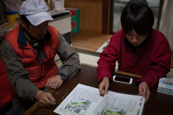 151116 - At his former home in Ryozen, Oguni, Mr Saiki Sugano explains to a Greenpeace radiation protection advisor how the decontamination effort at his home has been far from sufficient, and that it has since been recontaminated from the untouched surrounding land and forest. Greenpeace/Greg McNevin